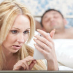 Woman Looking Through Man's Mobile Phone While He Is Asleep