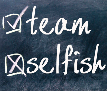 Signs of your own narcissism: Selfish ticked on blackboard and team crossed off.