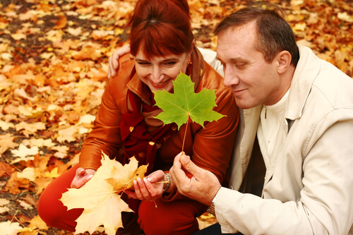 Mature Couple Enjoying Looking At Autumn Leaves