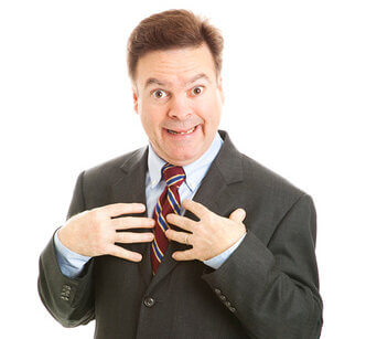 Businessman Looking Surprised And Pointing To Himself As If To Say